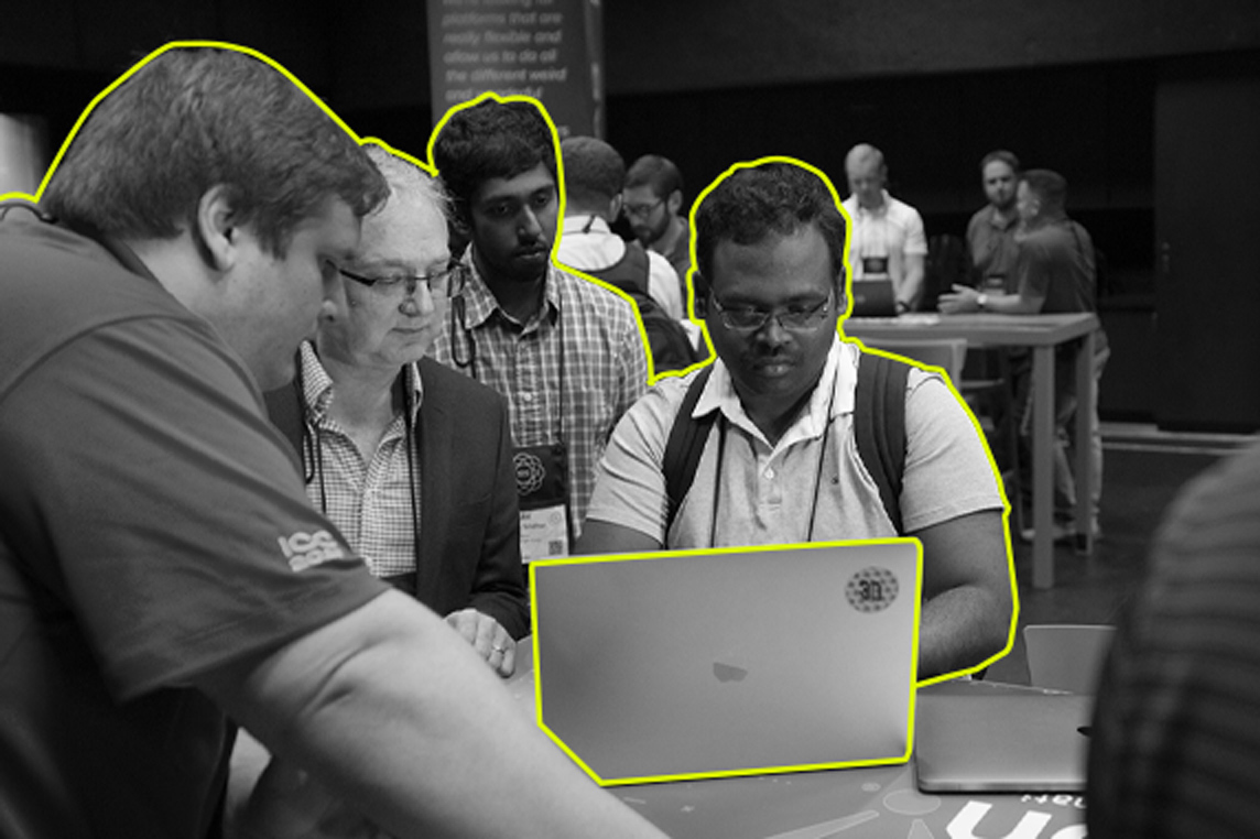 An Inductive Automation employee assists a conference attendee on his computer as others watch